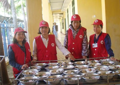 Chị Ngọc (ngoài cùng bên trái) chuẩn bị bữa cơm miễn phí cho bệnh nhân nghèo. Ảnh: M.S