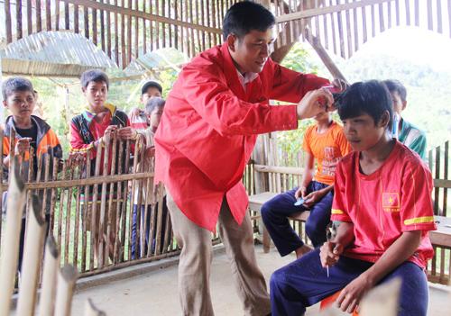 Thầy giáo Pơloong Nhao cắt tóc cho học sinh sau buổi học. Ảnh: ALĂNG NGƯỚC