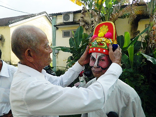 Cụ Trần Công Viên (82 tuổi, xã Quế Thuận, Quế Sơn) chuẩn bị cho diễn viên đội nhà trước khi lên sân khấu. Ảnh: LÊ QUÂN