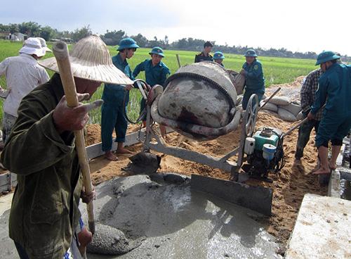 Lực lượng vũ trang huyện Quế Sơn giúp dân làm đường bê tông tại xã Hương An. Ảnh D.T