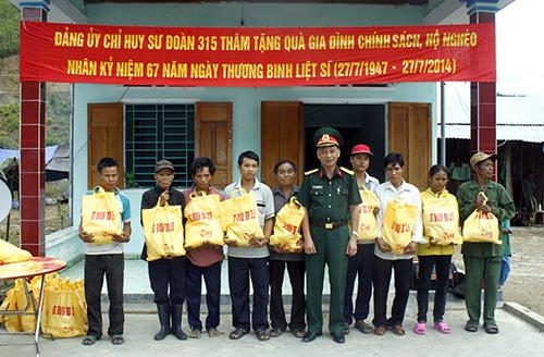Đại tá Nguyễn Tấn Thành - Chính ủy Sư đoàn 315 tặng quà gia đình chính sách tại huyện Nam Trà My. Ảnh: K.TUÂN