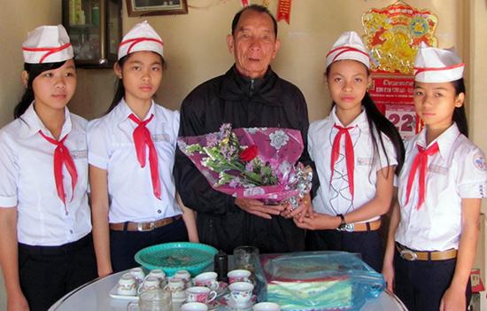 Học sinh Truờng THCS Lê Văn Tâm tặng hoa anh hùng Nguyễn Thành Khối.