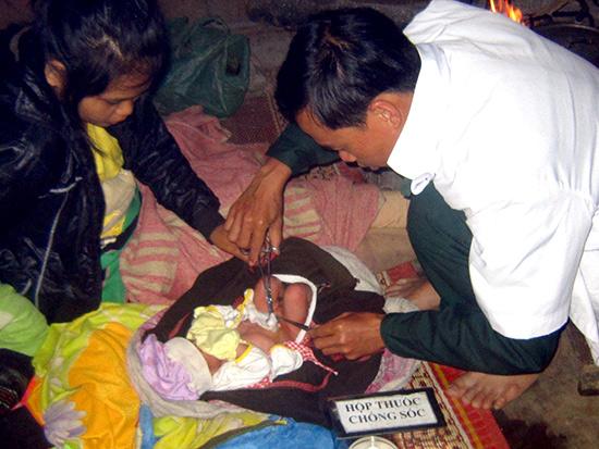 Bác sĩ Lê Ngọc Hóa chăm sóc em bé mới sinh.  Ảnh: ĐÌNH XUÂN