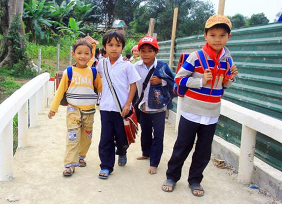 Học sinh thôn Vinh (xã Tà Pơơ) vui bước đến trường trên cây cầu Coor Dênh. Ảnh: ALĂNG NGƯỚC