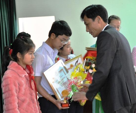 Chủ tịch UBND huyện Phú Ninh - Nguyễn Phi Thạnh trao Giải thưởng Phan Châu Trinh cho cá nhân có thành tích xuất sắc trong giảng dạy, nghiên cứu, học tập vào ngày 12.2.2015. Ảnh: X.NGHĨA
