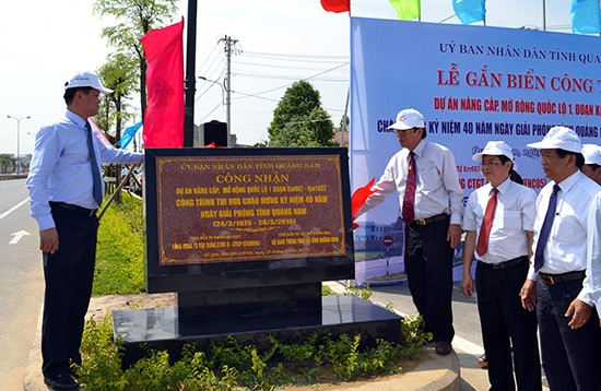 """Fixing the plate """"Celebrating Quang Nam province's Liberation Day"""" for the construction of the  National Highway 1A enlarging project . Photo: C.Tu"""