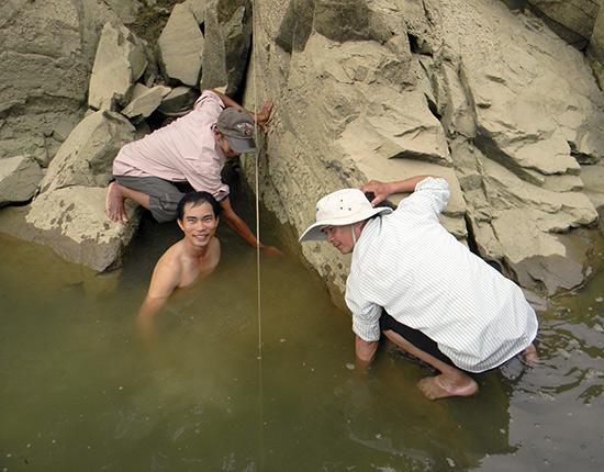 Các nhà nghiên cứu đang tiến hành đo đạc bia ký Chăm trên sông Thu Bồn. Ảnh: N.T.Hỷ