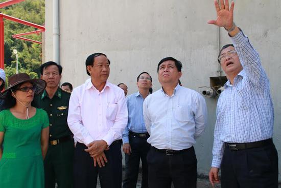 Thứ trưởng Nguyễn Chí Dũng (giữa) và Chủ tịch UBND tỉnh Đinh Văn Thu nghe nhà thầu báo cáo tiến độ thi công dự án. Ảnh: HUỲNH CHÍN