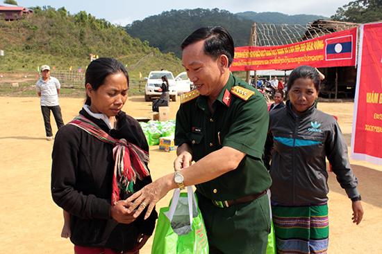 Đại tá Đoàn Thế Tùng, Phó Chính ủy Bộ CHQS tỉnh tặng quà cho bà con các bộ tộc Lào anh em. Ảnh: THANH TUẤN