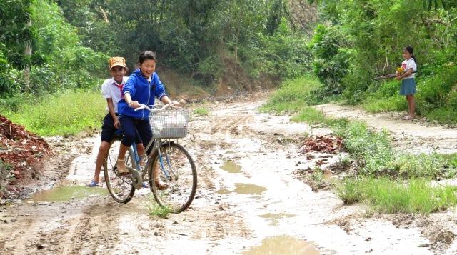 Trẻ em thôn Trung An, xã Quế Trung hằng ngày phải lặn lội đi học trên tuyến đường ĐT 610  mưa lầy nắng bụi, đá lởm chởm. Hoàng Liên