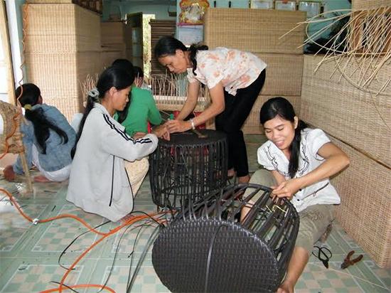 Chị Hồng Anh (áo hoa) hướng dẫn kỹ thuật đan giỏ cho các lao động nữ