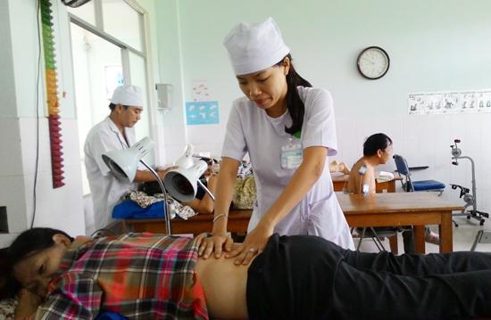 Kỹ thuật viên Khoa Phục hồi chức năng chăm sóc bệnh nhân. Ảnh: CHÂU NỮ
