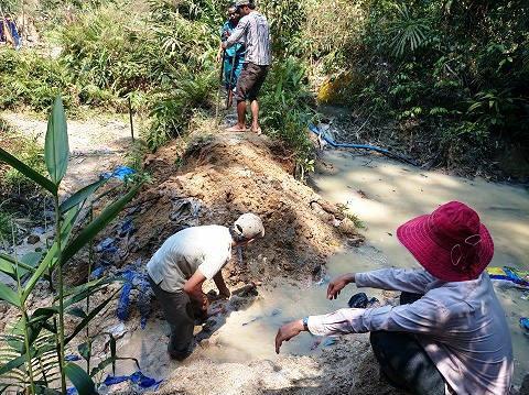 Tổ công tác đang lấp lại hồ chứa nước đào trái phép trong rừng phòng hộ Sông Tranh. Ảnh do Sở Tài nguyên - môi trường cung cấp.