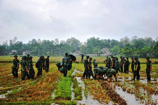 Cán bộ, chiến sĩ Tiểu đoàn vượt sông 25, Lữ đoàn Công binh 270 giúp nhân dân dồn điền đổi thửa. Ảnh: N.Đ.N
