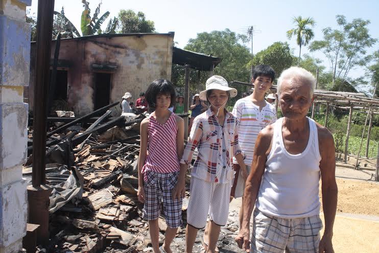 Cụ Trung và gia đình con trai bên căn nhà cháy rụi.