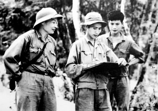 Họa sĩ Giang Nguyên Thái (giữa) ký họa ở chiến trường khu 5, ảnh tư liệu của họa sĩ Giang Nguyên Thái.