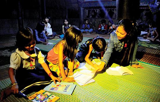 Blướch Thị Bloó (thôn Blừa) dạy các em nhỏ học ở gươl thôn A Rớh. Ảnh: XUÂN KHÁNH