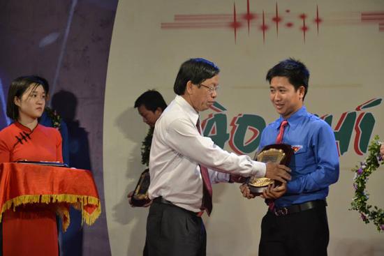 Bí thư Tỉnh ủy Lê Phước Thanh tặng biểu trưng cho đảng viên trẻ Phạm Minh Thành. Ảnh: HỒNG CƯỜNG