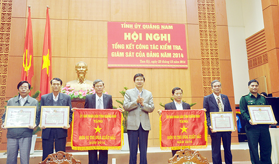 Phó Bí thư Thường trực Tỉnh ủy Nguyễn Ngọc Quang tặng cờ và bằng khen của UBND tỉnh cho các tập thể có thành tích xuất sắc trong công tác KTGS năm 2014. Ảnh: NG.ĐOAN