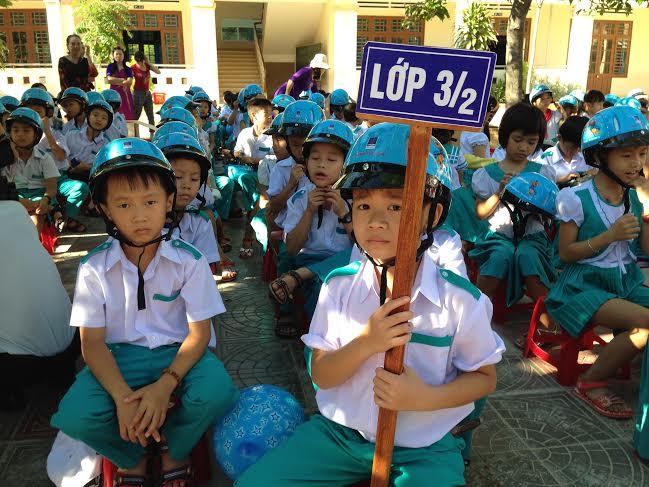 Trao mũ bảo hiểm cho các em học sinh.