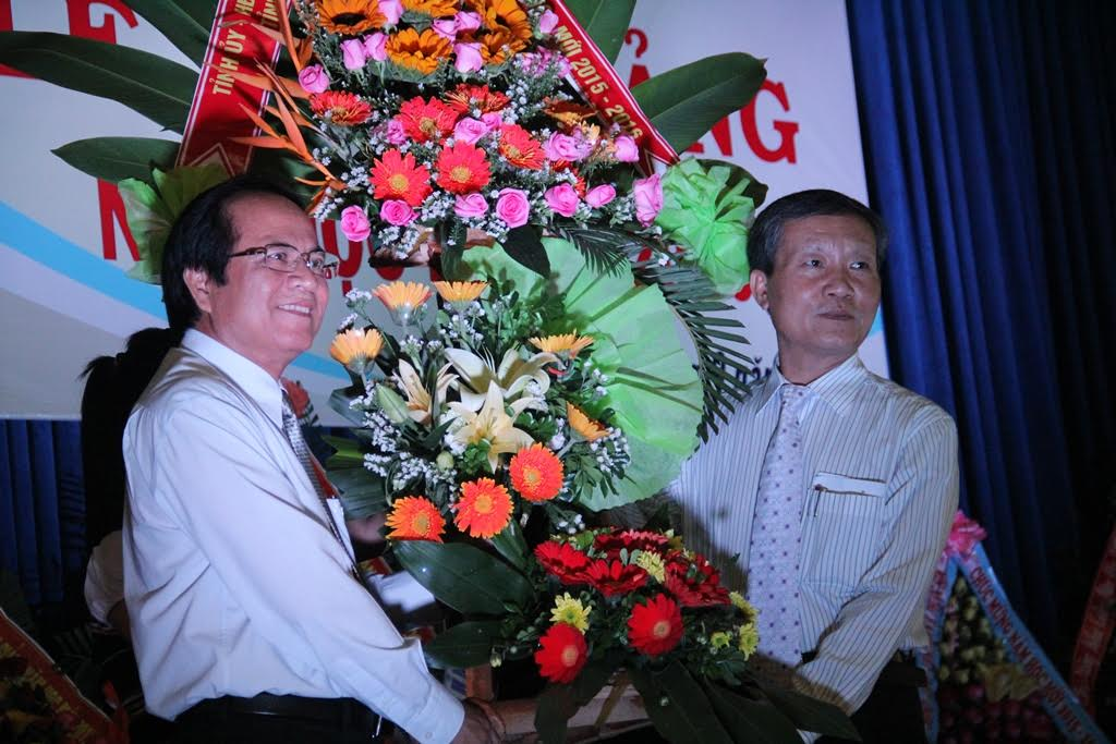 Phó Chủ tịch UBND tỉnh Trần Đình Tùng trao hoa chúc mừng thầy trò  trường Phổ thông DTNT tỉnh trong ngày khai giảng. Ảnh: ALĂNG NGƯỚC