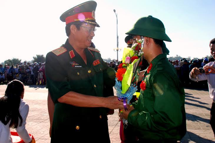 Thiếu tướng Trần Quang Phương - Bí thư Đảng ủy, Chính ủy Quân khu 5 tặng hoa cho các thanh niên nhập ngũ.