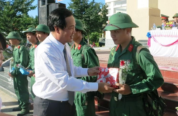 Phó Chủ tịch Thường trực UBND tỉnh Huỳnh Khánh Toàn tặng hoa chúc mừng các thanh niên lên đường làm nhiệm vụ. Ảnh: THU PHƯƠNG