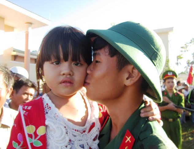 Tân binh Nguyễn Đắc Toàn (Quế Châu, Quế Sơn) hôn cháu trước khi lên đường. Ảnh: DUY THÁI