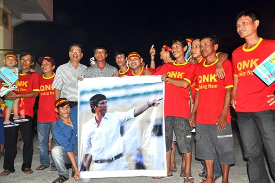 HLV Vũ Quang Bảo (thứ 4 từ trái sang) cùng các cổ động viên Quảng Nam giương bức chân dung của mình trong ngày QNK Quảng Nam lên V-League. Ảnh: AN NHI