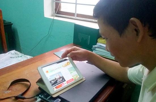 Ông Trần Vĩnh Thơ - Chủ tịch UBND xã Trà Don thao tác trên iPad để tiếp nhận thông tin từ huyện.    Ảnh: XUÂN KHÁNH