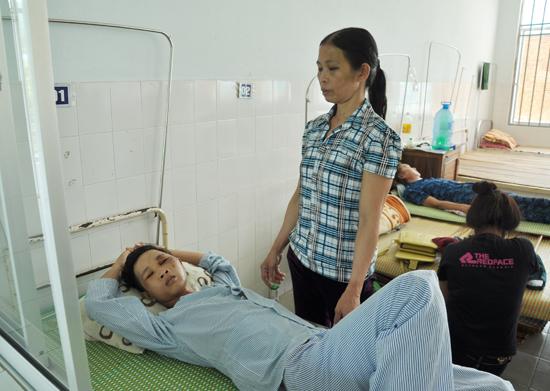 Bà Võ Thị Kim chăm sóc con trai bị tai nạn tại Bệnh viên Đa khoa Quảng Nam. Ảnh: H.L