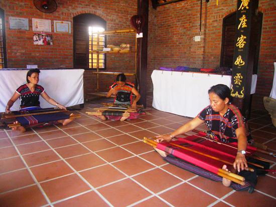 Các nghệ nhân Cơ Tu đang trình diễn nghề dệt thổ cẩm tại không gian Làng lụa Hội An. Ảnh: ĐÕ HUẤN