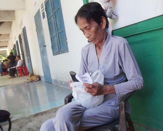 Bà Văn Thị Năm vui mừng khi nhận được tiền và quà từ nhóm thiện nguyện. Ảnh: T.L.L