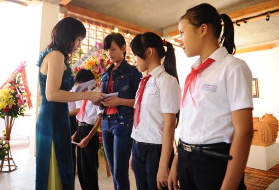 Họa sĩ Bạch Hoàng Anh trao học bổng cho những học sinh nghèo vượt khó học giỏi. Ảnh Minh Hải