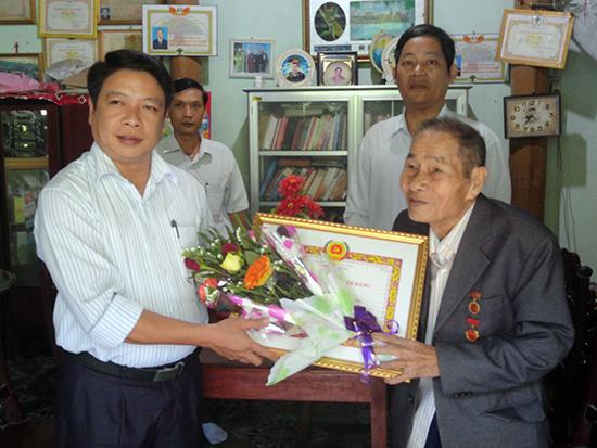 Phó Bí thư Huyện ủy Phú Ninh - Bùi Võ Quảng trao Huy hiệu 70 năm tuổi Đảng cho ông Vũ Minh Tuân.