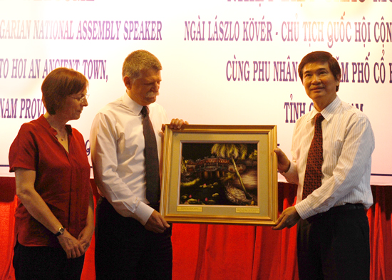 The Secretary of Quang Nam province (right) offers Mr Laszlo Kover an embroidery picture of Japanese Brigde.