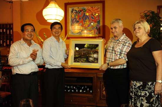 Secretary Nguyen Ngoc Quang offers President Milan Stech (behind, right) a picture of Japanese Brigde (Chua Cau).