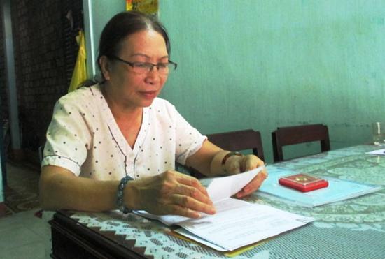 Cô Lê Thị Thanh Nga dù đã về hưu nhưng vẫn miệt mài xem bài trước khi đến lớp dạy hè.