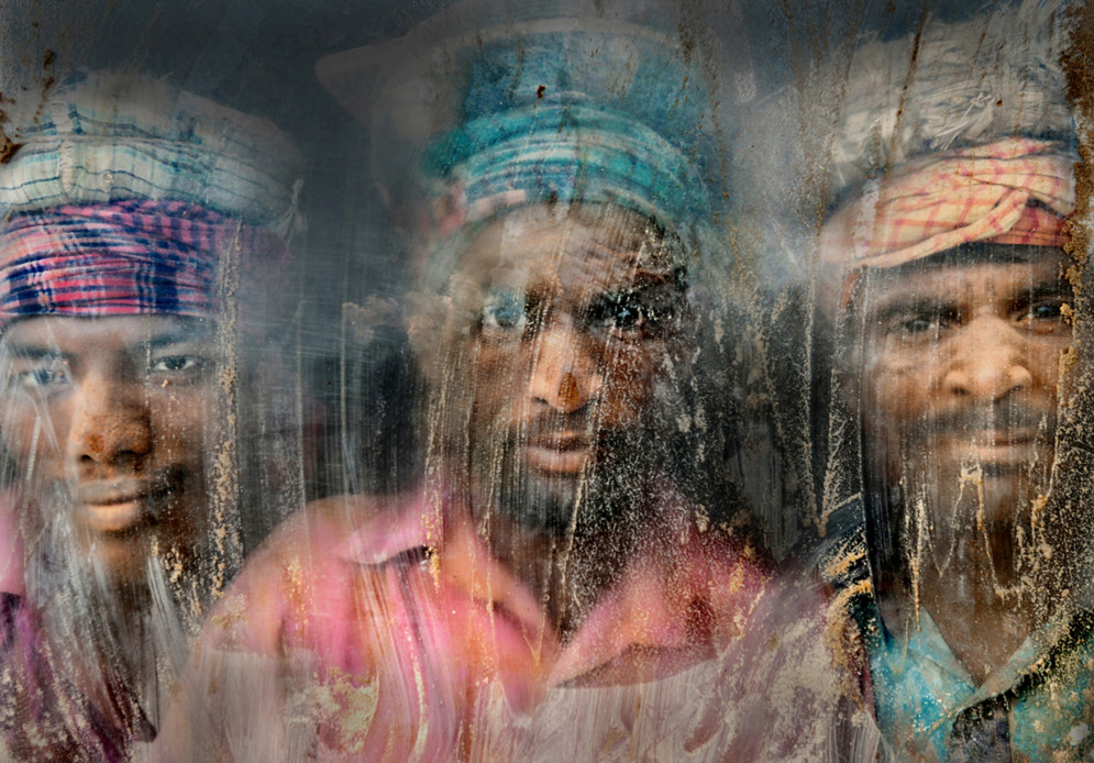 A gravel crushing workplace remains full of dust and sand. Three gravel workmen are looking through the window glass. #  © Faisal Azim