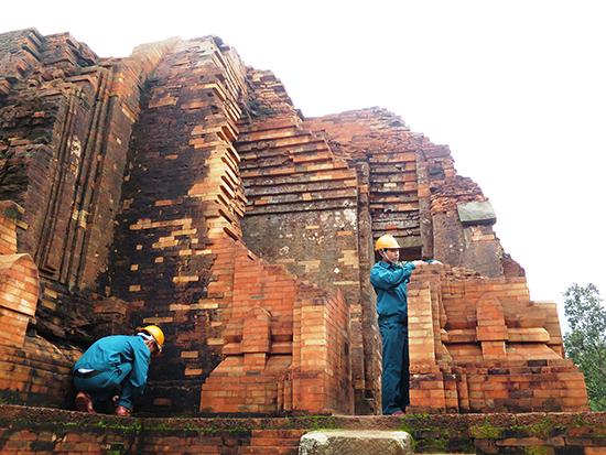 Những người thợ di sản - được Quỹ Lerici cấp chứng chỉ hành nghề đang xem lại những mảng tường do họ thực hiện trùng tu ở nhóm tháp G. Ảnh: LÊ QUÂN