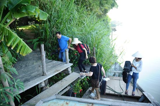 Du khách vượt sông tìm đến làng: Ảnh: Minh Hải