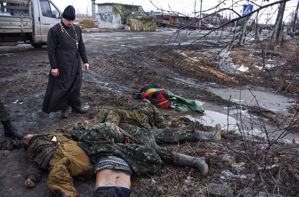 An Orthodox priest stands next to the bodies of Ukrainian soldiers on a check-point captured by pro-Russian rebels at the town of Krasniy Partizan, eastern Ukraine, on January 24, 2015. # Mstyslav Chernov / AP