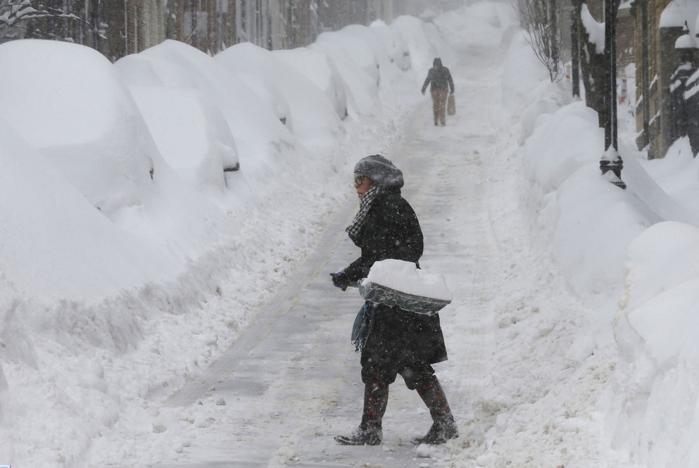 A woman shovels snow on Joy Street during a winter blizzard in Boston, Massachusetts, on February 15, 2015. The U.S. Northeast faced several major storms over the winter, burying many areas in several feet of snow and bringing normal life to a standstill. # Brian Snyder / Reuters