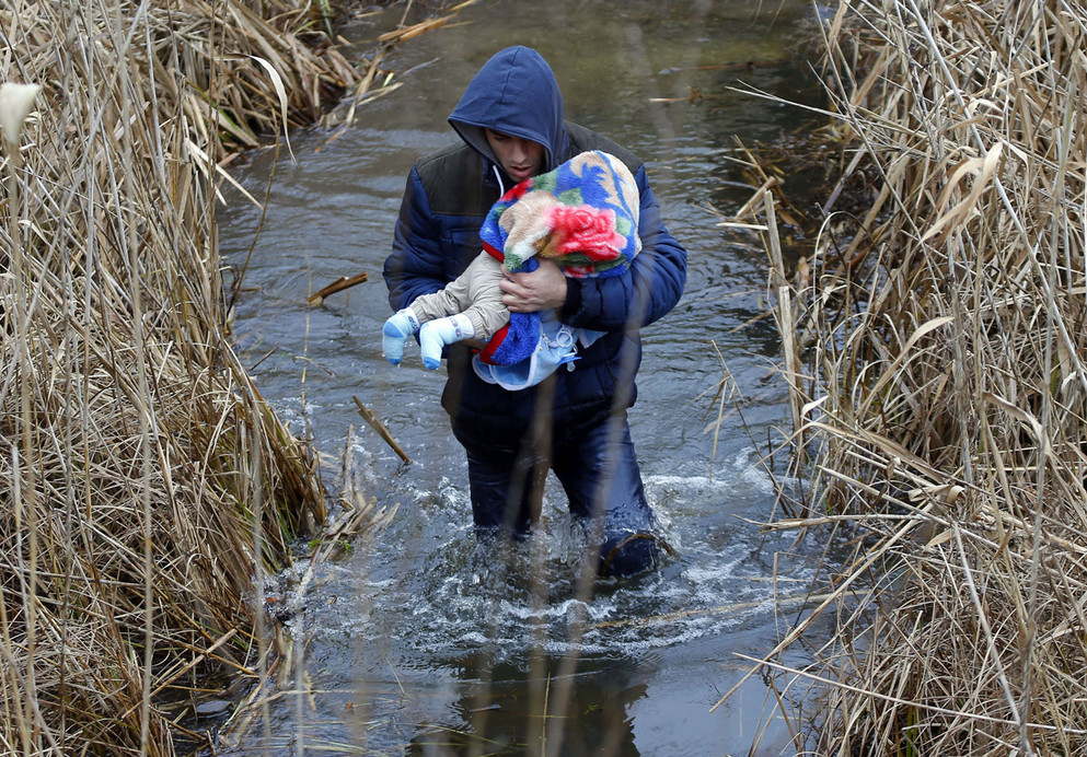 A Kosovo man carries his baby as he crosses illegally the Hungarian-Serbian border near the village of Asotthalom on February 6, 2015. The European Union is experiencing a steep rise in the number of Kosovo citizens smuggling themselves into the affluent bloc, with 10,000 filing for asylum in Hungary in just one month this year compared to 6,000 for the whole of 2013. It follows a relaxation of travel rules allowing Kosovars to reach EU borders via Serbia and has coincided with political turmoil and street unrest in Kosovo fueled by poverty, high unemployment, and economically debilitating corruption. # Laszlo Balogh / Reuters
