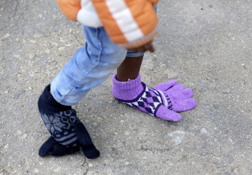 "A child wears gloves on her feet as she arrives with her mother on the boat ""Nos Taurus Genova"" at the Sicilian harbor of Pozzallo, on February 16, 2015. Better weather had encouraged migrants to make the perilous journey from North Africa, where a breakdown of order in Libya has made it almost impossible to police the traffickers who pack people onto rickety boats. # Alessandro Bianchi / Reuters"
