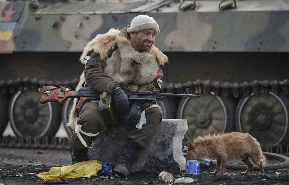 A Russia-backed rebel rests as a dog eats from a can in Debaltseve, Ukraine, on February 20, 2015. After weeks of relentless fighting, the embattled Ukrainian rail hub of Debaltseve fell to Russian-backed separatists, who hoisted a flag in triumph over the town. The Ukrainian president confirmed that he had ordered troops to pull out and the rebels reported taking hundreds of soldiers captive. # Vadim Ghirda / AP