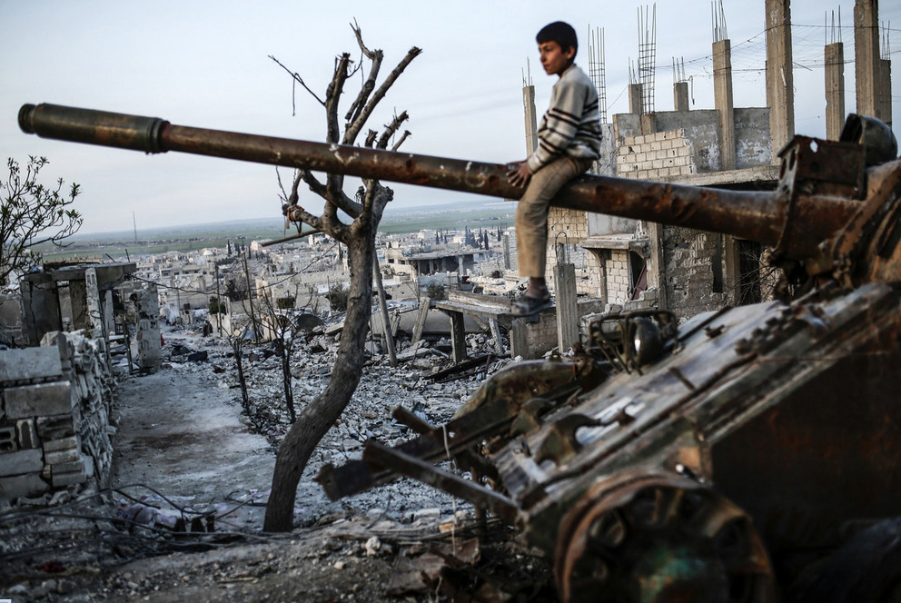 A Syrian Kurdish boy sits on a destroyed tank in the Syrian town of Kobane, also known as Ain al-Arab, on March 27, 2015. ISIS fighters were driven out of Kobane on January 26 by Kurdish and allied forces. # Yasin Akgul / AFP / Getty