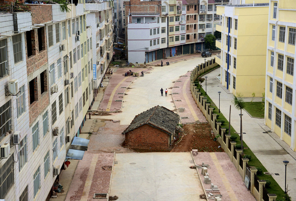 "A ""nail house,"" the last building in the area, sits in the middle of a road under construction in Nanning, Guangxi Zhuang Autonomous Region, China, on April 10, 2015. According to local media, the owner of the house didn't reach an agreement with the local authority about compensation of the demolition. # Reuters"