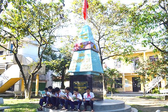 Học sinh Trường THCS Mỹ Hòa ôn bài dưới chân mô hình cột mốc chủ quyền quần đảo Trường Sa.Ảnh: K.KHIÊM