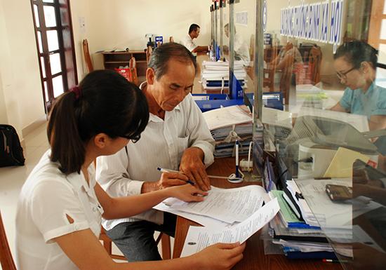 Hướng dẫn người dân điền hồ sơ tại bộ phận một cửa.